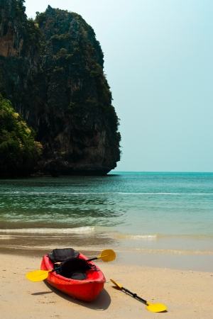 cayak: Tropical beach landscape with red canoe boat at ocean gulf under blue sky. Pranang cave beach, Railay, Krabi, Thailand