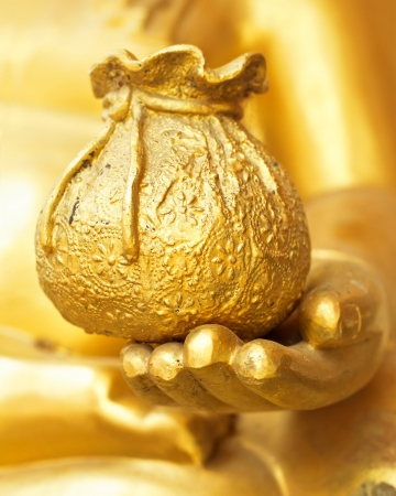 Concept idea of good luck, happiness, and healthy rich life. Close up hand of golden buddha statue holding pouch full of money photo