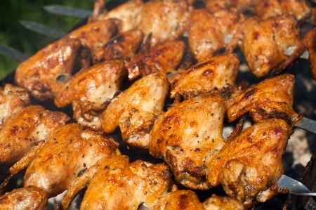 Cooking delicious juicy chicken wings at outdoors grill photo