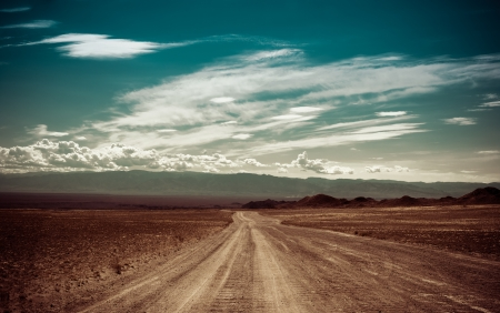 country western: Empty rural road going through prairie under cloudy sky in Charyn canyon  State National Paleontology Park in Kazakhstan  Vintage style processing image