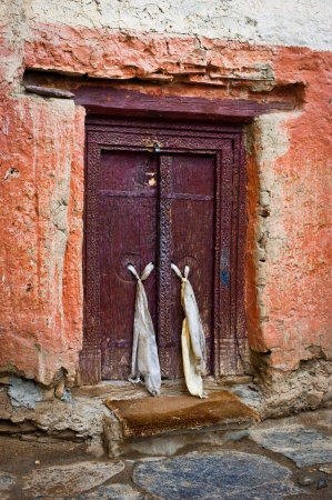 Old door at Buddhist monastery temple decorated with ancient doorknob and tassel. India, Ladakh, Lamayuru Gompa photo