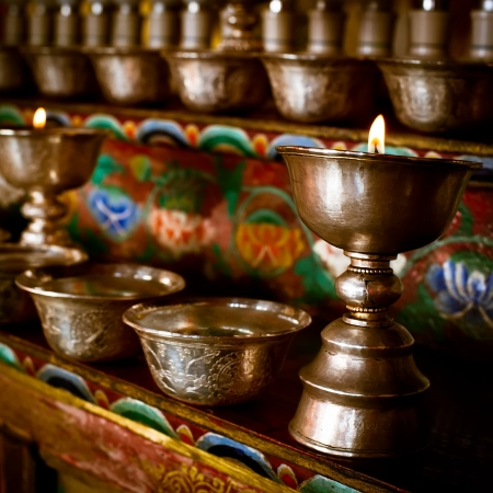Burning oil lamps and offering bowls at Buddhist monastery temple  India, Ladakh, Thiksey Gompa photo