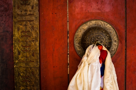 Old door at Buddhist monastery temple decorated with ancient doorknob and tassel. India, Ladakh, Diskit monastery photo