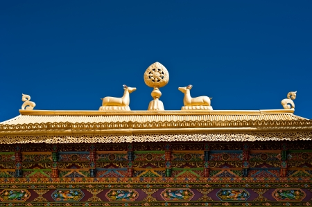 Buddhist symbols: Dharma-wheel and deer on decorated roof under blue sky at Thiksey Gompa. India, Ladakh, Thiksey Monastery photo