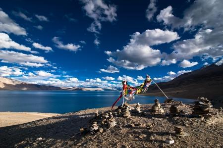 ladakh: Sunset view at Tso Moriri Lake with stone pyramid and Buddhist praying flags  Himalaya mountains landscape  India, Ladakh, altitude 4600 m