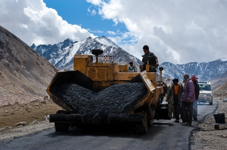 KHARDUNG LA PASS, INDIA - SEPTEMBER 12: Indian people working at road construction at Khardung La pass. The one main road at Himalaya mountains, altitude 5600 m. India, Ladakh, September 12, 2012