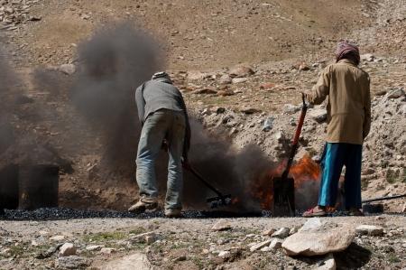 KHARDUNG LA PASS, INDIA - SEPTEMBER 12: Indian people working at road construction at Khardung La pass. The one main road at Himalaya mountains, altitude 5600 m. India, Ladakh, September 12, 2012