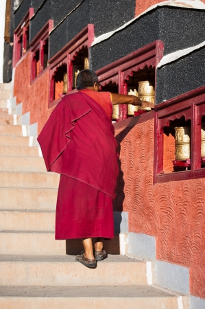 THIKSEY, INDIA - SEPTEMBER 13: Buddhist monk from Thiksey monastery in Himalaya mountains rotating praying wheel before morning puja ceremony on September 13, 2012 in Thiksey Gompa, Leh, Ladakh, india