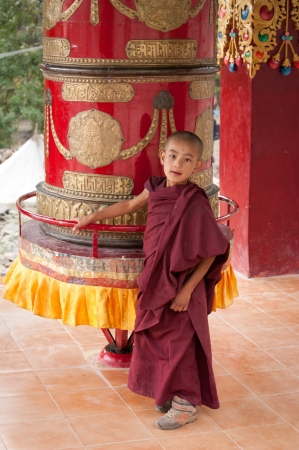 HEMIS, INDIA - SEPTEMBER 13: Unidentified tibetan boy, novice monk, student of Buddhist school at Hemis monastery, rotating praying wheel on September 13, 2012 in Hemis Gompa, Leh, Ladakh, india