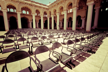 Rows of chairs at outdoors concert hall with ancient columns under cloudy sky. Thirumalai Nayak Palace. India, Madurai. Vintage style image Stock Photo - 23368614