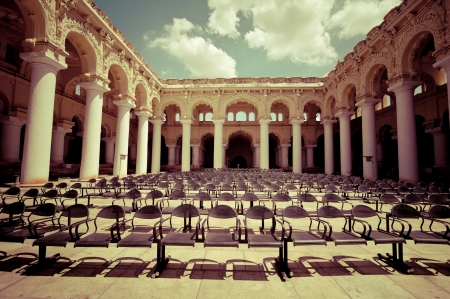 Rows of chairs at outdoors concert hall with ancient columns under cloudy sky. Thirumalai Nayak Palace. India, Madurai. Vintage style image photo