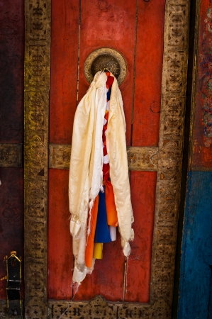 Old door at Buddhist monastery temple decorated with ancient doorknob and tassel. India, Ladakh, Thiksey Gompa photo