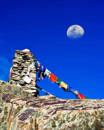 ladakh: Buddhist stone tower with praying flags and moon at Himalaya high mountain road pass at Manali - Leh highway over blue sky. India, Ladakh, altitude 4500m