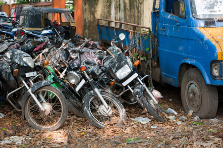 unwanted: Old broken motorbikes and car for recycling in junkyard. India