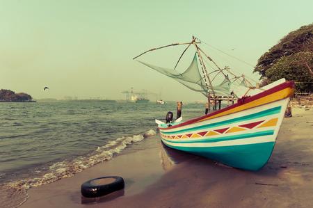 Ocean coast landscape with traditional Indian boat and chinese fishing nets at Cochin (Kochi). South India, Kerala, Kochin photo