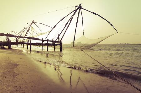 Sunset at tropical beach. Ocean coast landscape with chinese fishing nets silhouette at Cochin (Kochi). South India, Kerala, Kochin photo