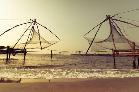 india fisherman: Sunset at tropical beach. Ocean coast landscape with chinese fishing nets silhouette at Cochin (Kochi). South India, Kerala, Kochin