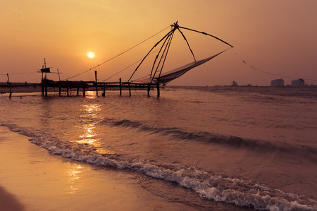 chinese fishing nets: Sunset at tropical beach. Ocean coast landscape with chinese fishing nets silhouette at Cochin (Kochi). South India, Kerala, Kochin