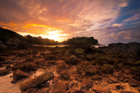 Ocean landscape of tropical beach with rocks and stones under colorful dramatic sunset sky. Cay at evening low tide. Thailand, Phuket photo