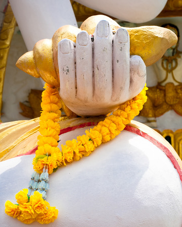 spiritual bless: Buddhas hand with flower garland in Wat Plai Laem Temple. Koh Samui island, Thailand Stock Photo