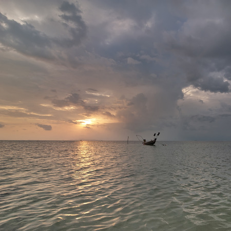 Sunset at tropical beach. Evening ocean landscape with Thai traditional boat  under dramatic stormy sky. Thailand, Koh Samui photo