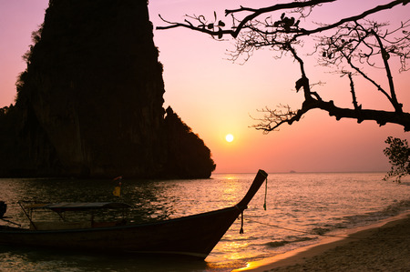 Sunset at tropical beach landscape with Thai traditional boat and tree. Rock formation island silhouette under evening sun at ocean coast . Pranang cave beach, Railay, Krabi, Thailand photo