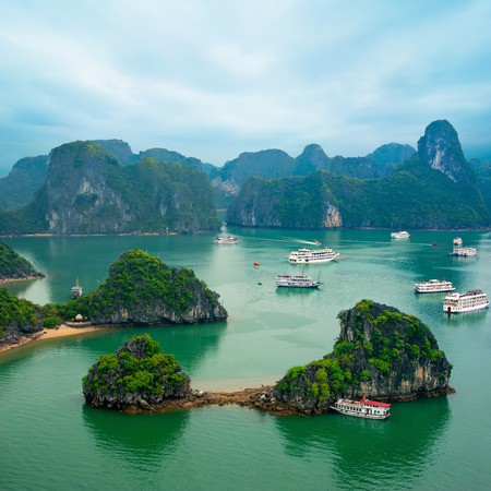 bay: Tourist junks floating among limestone rocks at early morning in Ha Long Bay, South China Sea, Vietnam, Southeast Asia. Two images panorama