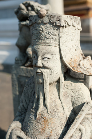 Statue of Chinese stone guardian at Wat Pho Temple  Thai traditional Buddhist architecture in Bangkok, Thailand photo