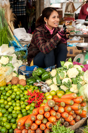 SIEM REAP, CAMBODIA - DEC 22, 2013: Unidentified Khmer woman selling greengrocery at traditional marketplace on Dec 22, 2013 in Siem Reap, Cambodia. Street food markets is popular tradition in asia