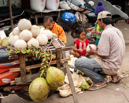 SIEM REAP, CAMBODIA - DEC 22, 2013: Unidentified Khmer family selling coconuts at traditional food marketplace on Dec 22, 2013 in Siem Reap, Cambodia. Street food markets is popular tradition in asia Stock Photo - 26278076