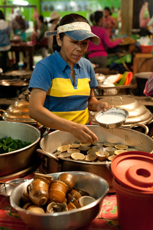 SIEM REAP, CAMBODIA - DEC 22, 2013: Unidentified Khmer woman selling traditional food at marketplace on December 22, 2013 in Siem Reap, Cambodia. Street food cooking and selling is a local tradition