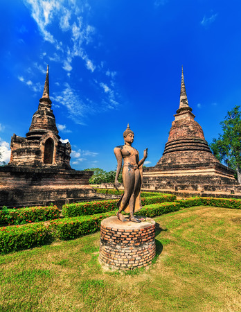 sukhothai: Ancient architecture of Buddhist temples in Sukhothai Historical Park  Statue of walking Buddha at Sa-Si Temple under blue sky  Thailand