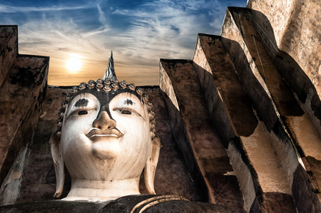 chum: Ancient architecture of Buddhist temples in Sukhothai Historical Park  Statue of  Buddha Phra Achana at Wat Si Chum Temple under sunset sky  Thailand Stock Photo