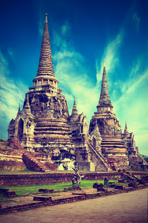 architecture ancient: Vintage style image of asian religious architecture. Ancient pagoda at Wat Phra Sri Sanphet temple under blue sky. Ayutthaya, Thailand Stock Photo