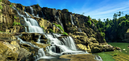 Tropical rainforest landscape panorama with flowing Pongour waterfall under blue sky. Da Lat, Vietnam photo
