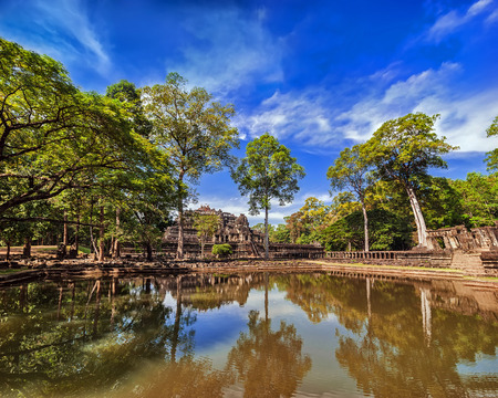 reap: Ancient Khmer architecture. Outdoor park landscape with lake and panorama view of Baphuon temple ruins at Angkor Wat complex, Siem Reap, Cambodia Stock Photo