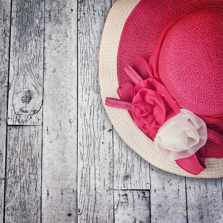 pink hat: Pink summer hat with silk roses flowers at grunge wooden texture of old weathered wall. Image in vintage style