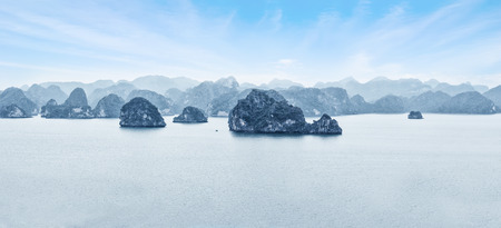 halong: Early morning landscape with blue fog and limestone rocks at Ha Long Bay, South China Sea, Vietnam, Southeast Asia. Travel background, two images panorama Stock Photo