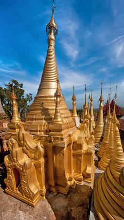 Golden stupas of Shwe Indein Pagoda over blue sky. Indein village, Inle Lake, Shan State, Myanmar (Burma) photo