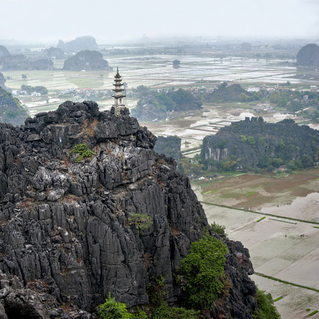 valley of the temples: Amazing panorama view of the rice fields, limestone rocks and mountaintop Pagoda from Hang Mua Temple at the early rainy morning  Ninh Binh, Vietnam