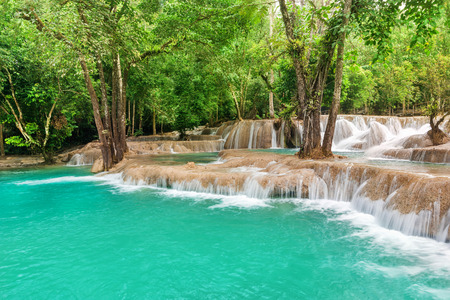 Jangle landscape with amazing turquoise water of Kuang Si cascade waterfall at tropical rain forest near Luang Prabang, Laos photo