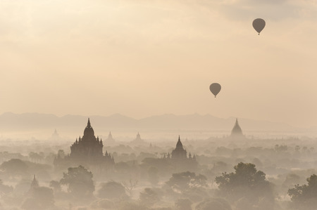 Silhouettes of balloons and ancient Sulamani and Tha Beik Hmauk Gu Hpaya at amazing sunrise. Architecture of old Buddhist Temples at Bagan Kingdom, Myanmar (Burma). Travel landscapes and destinations photo