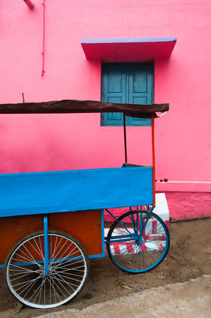 Bright colors of Indian street life. Colorful composition of empty blue vendor cart near pink painted wall with window. South India, Tamil Nadu photo