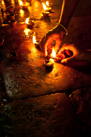 People burning oil lamps as religious ritual in Hindu temple. India photo