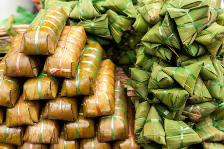 Traditional asian dessert made from rice dough and sweet coconut wrapped in banana leaf photo