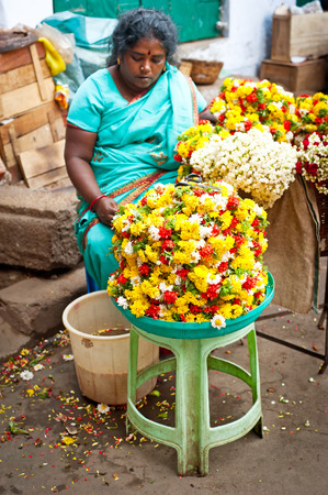 TRICHY, INDIA - FEBR 14: Indian women selling colorful flower garland at street market place for religion ceremony or fashion decoration on Febr 14, 2013. India, Tamil Nadu, Thanjavur (Trichy)