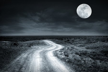 moon  desert: Empty rural road going through prairie at full moon night with dramatic cloudy sky