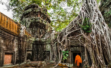 Buddhist monk at Angkor Wat  Ancient Khmer architecture, Ta Prohm temple ruins hidden in jungles  Popular travel destination at Siem Reap, Cambodia photo
