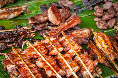 Traditional asian food at market. Delicious spicy grilled pork meat photo