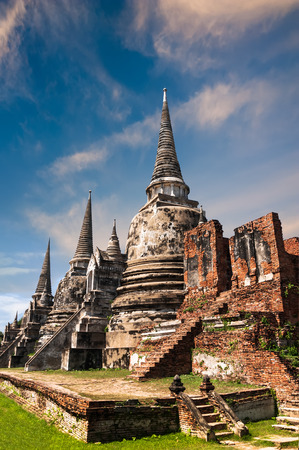 Asian religious architecture. Ancient Buddhist pagoda ruins\ at Wat Phra Sri Sanphet temple under sunset sky. Ayutthaya,\ Thailand travel landscape and destinations
